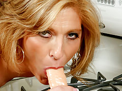 Dee Dee grabs a bite of rubber cock from her kitchen pantry